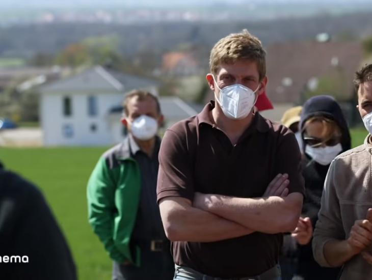 Eine Gruppe Landwirte mit FFP2-Masken blickt entschlossen auf dem boden:ständig-Feldtag in Obernzenn. Am Bildrand sind die Logos des Bayerischen Rundfunk zu sehen, woran man erkennt, dass es sich um einen screenshot aus einer Sendung handelt.