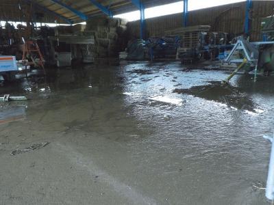 Wasser steht in einer Lagerhalle.
